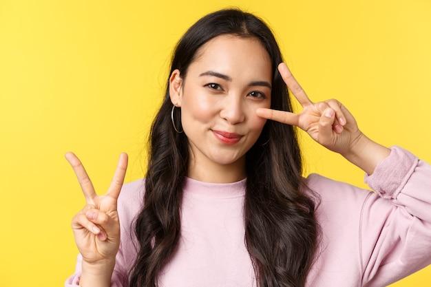 사람들의 감정, 라이프 스타일 여가 및 아름다움 개념. 노란색 배경 광고 제품 위에 서서 평화 신호를 보내고 귀엽게 웃고 있는 귀여운 일본 소녀.
