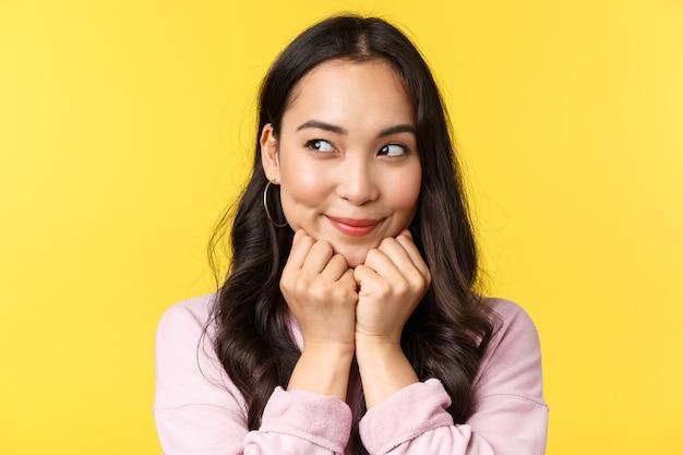 Эмоции людей, досуг образа жизни и концепция красоты. у глупой мечтательной азиатской девушки есть интересная идея, представляя что-то, как выглядывающее влево и улыбающееся, замышляющий план, желтый фон.