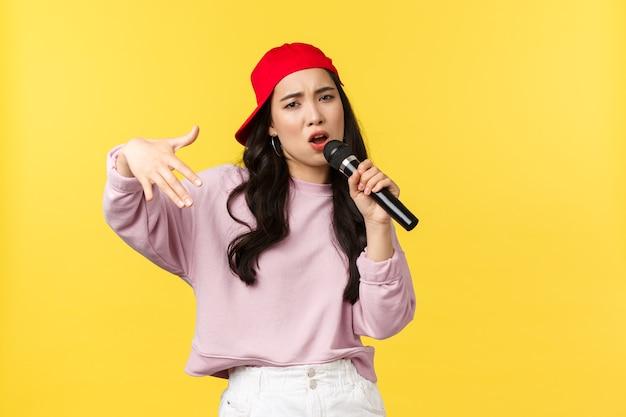 사람들의 감정, 라이프 스타일 여가 및 아름다움 개념. 빨간 모자를 쓴 세련되고 멋진 어린 소녀 래퍼, 노래 부르고 몸짓, 마이크 연주, 노란색 배경 서.