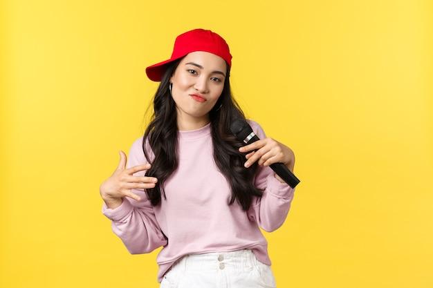 人々の感情、ライフスタイルのレジャーと美しさの概念。赤い帽子をかぶったスタイリッシュでクールな若い女の子のラッパー、歌を歌い、身振りで示す、マイクで演奏、黄色の背景に立っています。