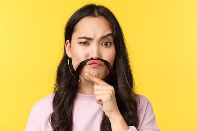 Эмоции людей, досуг образа жизни и концепция красоты. задумчивая смешная девушка делает поддельные усы из волос и смотрит в камеру осуждающе или подозрительно, думая, желтый фон.