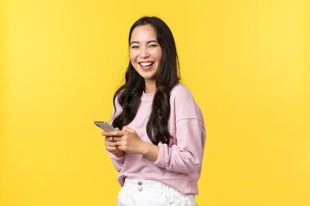 Emozioni delle persone, tempo libero lifestyle e concetto di bellezza. donna asiatica felice sorridente allegra, gira la macchina fotografica e ride dopo aver letto un post divertente sull'app dei social media, tenendo in mano lo smartphone.