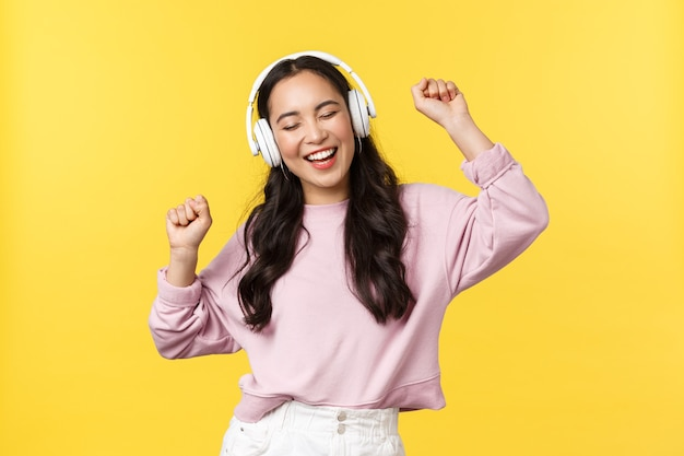 People emotions, lifestyle leisure and beauty concept. joyful pretty asian woman in wireless headphones listening music, dancing excited with closed eyes and happy smile, listen favorite song.