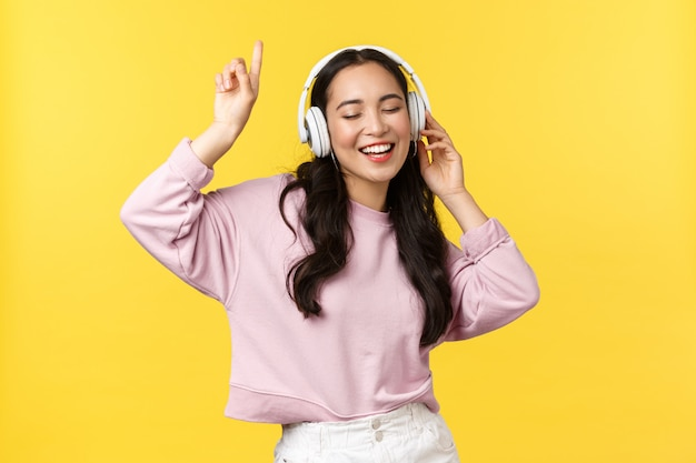 People emotions, lifestyle leisure and beauty concept. pretty happy asian woman in wireless headphones, listening music and dancing, singing along, enjoying summer