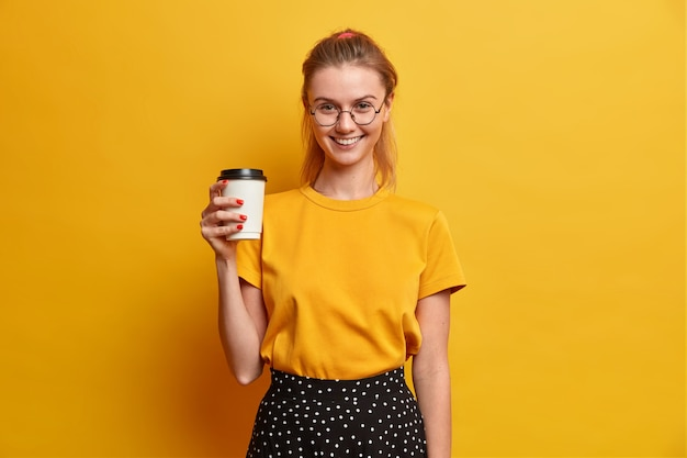 People emotions lifestyle spare time concept. glad young european woman smiles happily holds cup of takeaway coffee drinks aromatic beverage dressed casually isolated over yellow wall.