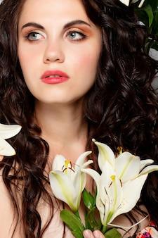 人、感情、自然、美しさ、花、ライフスタイルのコンセプト-美容少女は美しい花を手に取ります。吹く花。花のある髪型。夏の妖精の肖像画。長いパーマの髪。