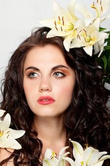 사람, 감정, 자연, 아름다움, 꽃, 생활 방식 개념 - 미인 소녀는 아름다운 꽃을 손에 듭니다. 부는 꽃. 꽃과 헤어스타일입니다. 여름 요정 초상화입니다. 긴 파마 머리.