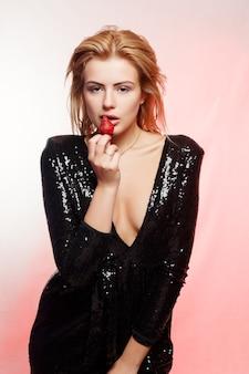 사람, 감정, 자연, 음식, 아름다움 및 라이프 스타일 개념 - 딸기와 섹시한 금발. 매혹적이고 관능적인 젊은 여성. 분홍색 배경, 마젠타색, 딸기에 메이크업 블랙 드레스를 입은 여자
