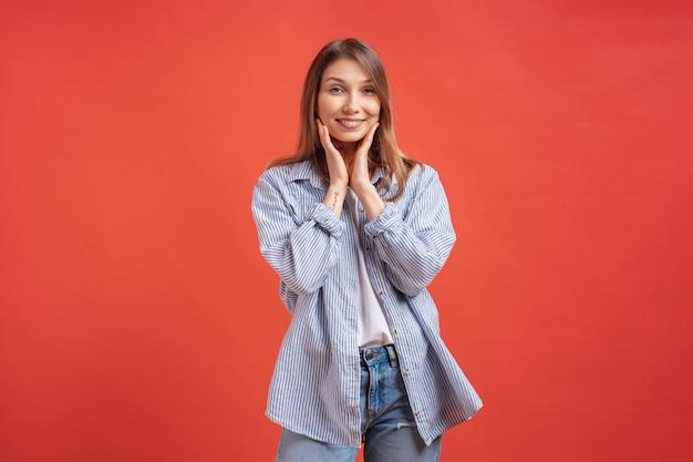 人々の感情-赤い壁の上の驚きの肯定的な女の子の肖像画