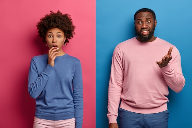 People and emotions. puzzled afro american girl gasps with wonder, displeased man with beard raises palm