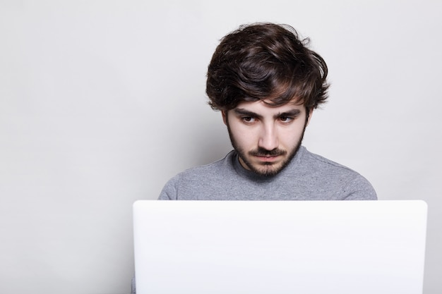 People, emotions, technology, education. serious stylish guy with trendy beard working with his laptop.