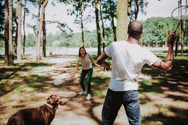 People enjoy badminton in park playful labrador
