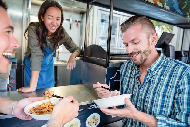 People enjoy eating pasta at counter of food truck