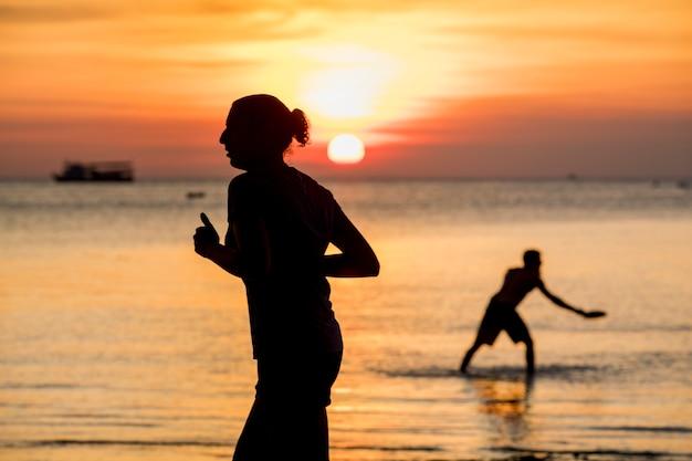 人々は日没でビーチを楽しむ