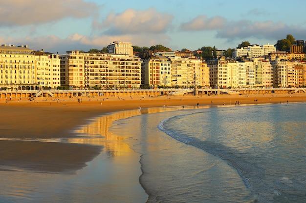 사람들은 스페인 산세바스티안 바스크 지방의 라 콘차 해변에서 휴가를 즐기고 있습니다.