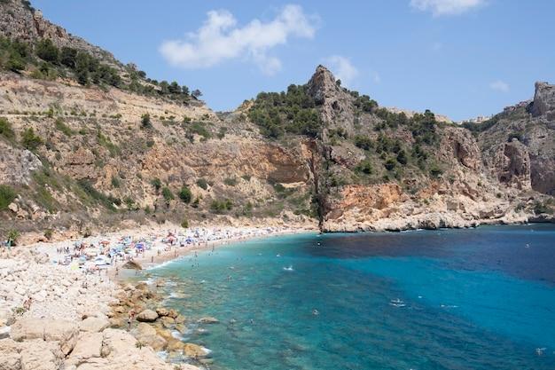 崖に囲まれた天気の良い日に地中海のビーチを楽しむ人々