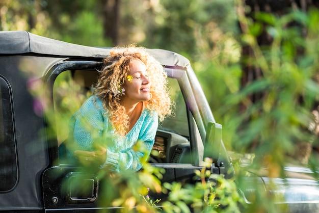 自由と旅行ライフスタイルの良さを楽しんでいる人々-車の窓の外の陽気な幸せな女性は太陽を楽しんでいます-全地形対応車で森の中での代替のロードトリップ休暇