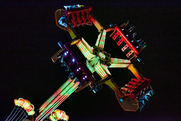 People enjoying themselves on a fairground attraction. night photography. colored lights.