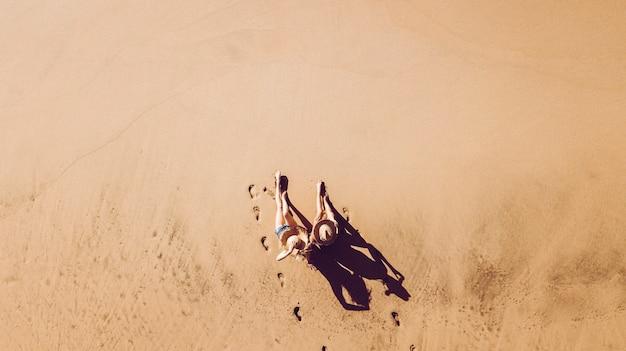 Люди наслаждаются отдыхом на пляже в курортном отеле, вид с вертикальной воздушной точки зрения - пара девушек садится на песок во время летних каникул - туристы на открытом воздухе сверху - живописная концепция