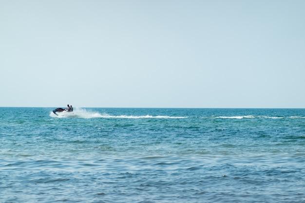 晴れた日に青い海でウォータージェットスキーを楽しむ人々。