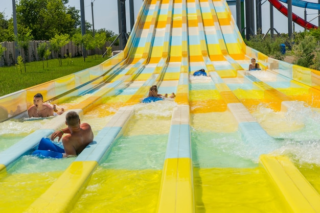People enjoying a water slide at a resort or amusement park sliding down towards the camera along colorful lanes