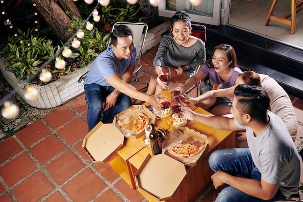 Люди наслаждаются вином и едой на заднем дворе