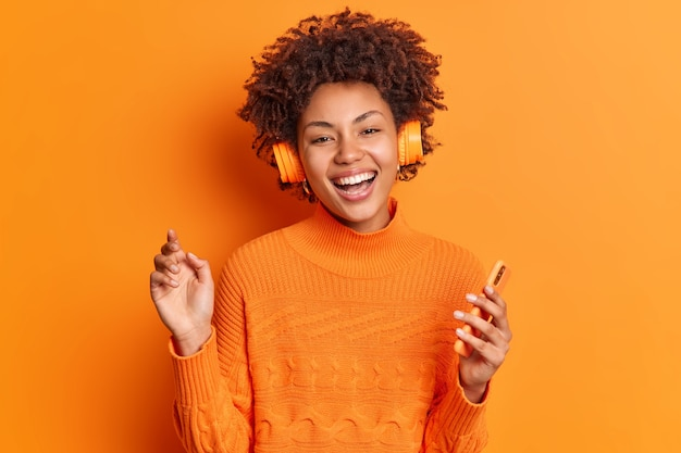 People entertainment and hobby concept. cheerful young african american woman with curly hair holds modern smartphone listens music via stereo headphones poses against vivid orange background
