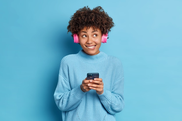 People entertainment and leisure concept. pleased african american woman bites lips wears stereo headphones listens audio track enjoys favorite melody dressed in sweater