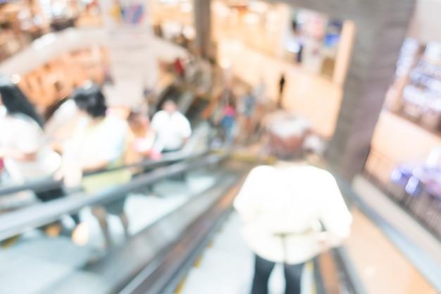 Persone su una scala mobile in un centro commerciale di sfocatura