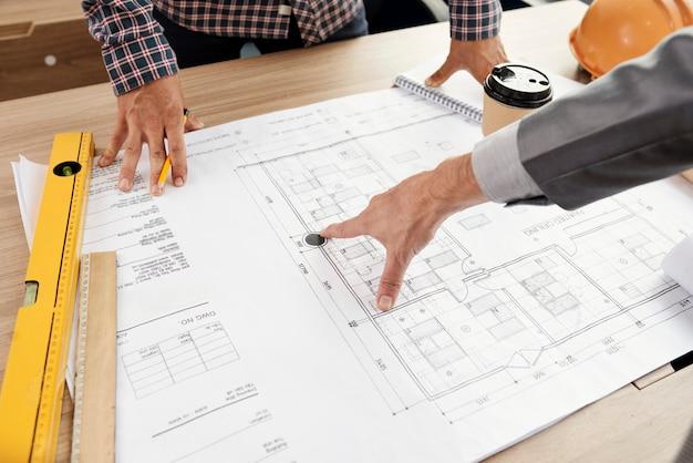 Люди, изучающие план строительства