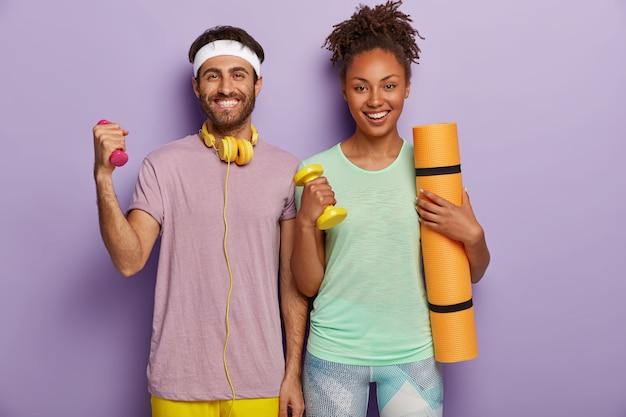사람, 운동 및 스포츠 개념. 행복한 백인 남자와 어두운 피부를 가진 여자는 아령을 들고, 피트니스 매트를 들고, 이빨 미소를지었습니다.