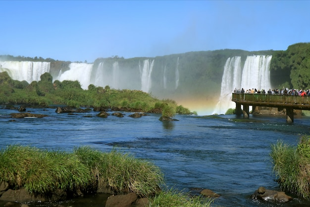 People exploring the powerful iguazu falls with a gorgeous rainbow from the boardwalk, brazil