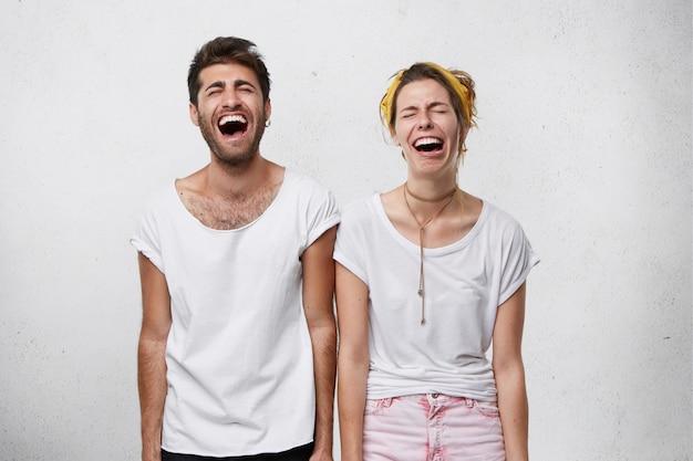 사람, 얼굴 표정 및 신체 언어 개념. 젊은 여성과 그녀의 남자 친구가 입을 크게 벌리고 눈을 감고 웃고