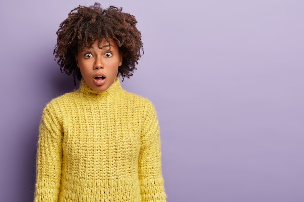 People, facial expressions concept. stupefied dark skinned female model opens mouth, expresses shock, hears bad latest news, wears yellow clothes, isolated over purple wall