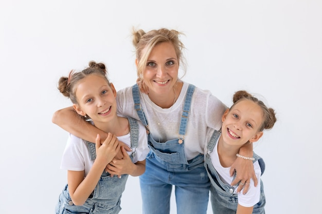 Концепция людей, семьи и детей - сестры-близнецы с их мамой на белой поверхности.