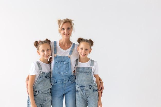 Концепция людей, семьи и детей - сестры-близнецы с их мамой на белой стене с копией пространства.