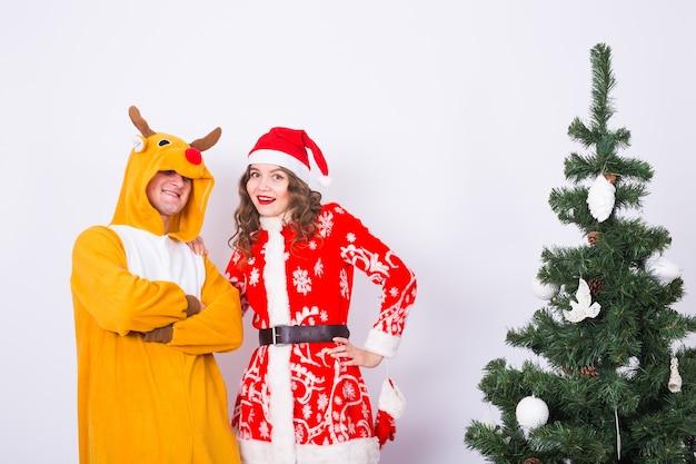 Люди, семья и рождественские концепции - прекрасная пара в рождественских костюмах возле елки на белом фоне.