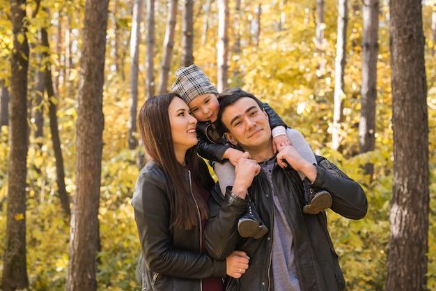 人、家族、レジャーのコンセプト-秋の公園に立って楽しんでいる家族。