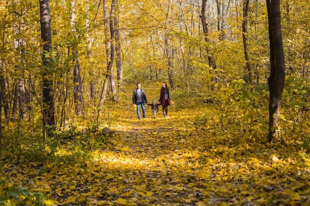 人、家族、レジャーのコンセプト-秋の公園を歩いている娘と幸せな家族。