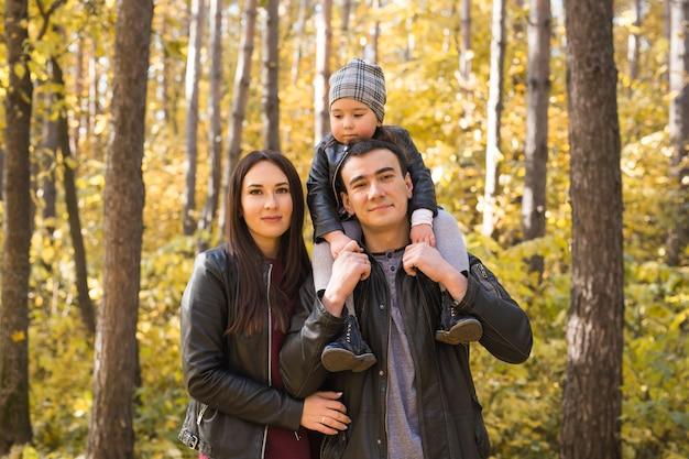 人々、家族、レジャーのコンセプト-母、父、そして小さな娘は秋の公園で楽しんでいます。