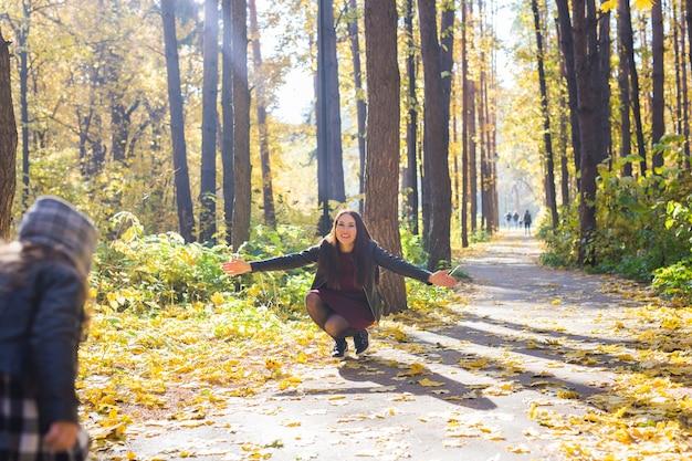 人、家族、レジャーのコンセプト-若い母親は秋の公園で娘と楽しんでいます