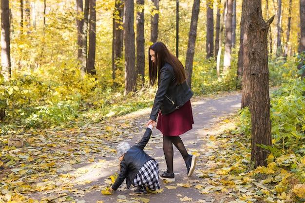 人、家族、レジャーのコンセプト-秋の公園で娘と一緒に歩いている若い母親。