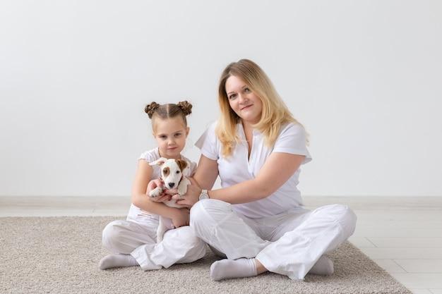 사람, 가족 및 애완 동물 개념-강아지 잭 러셀과 함께 바닥에 앉아 어머니와 딸