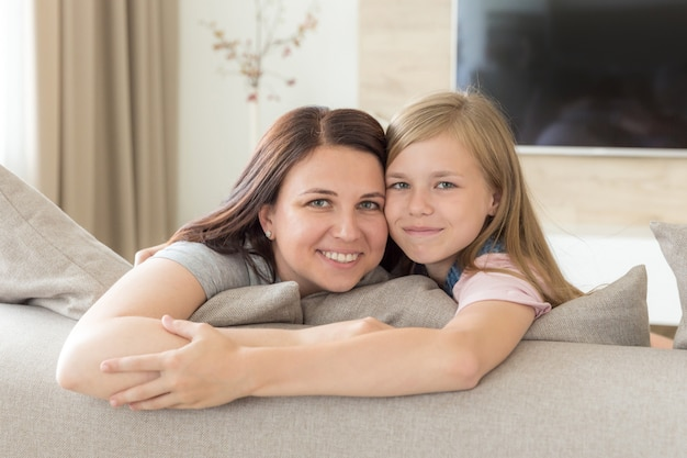 People and family concept   happy smiling girl with mother hugging on sofa at home