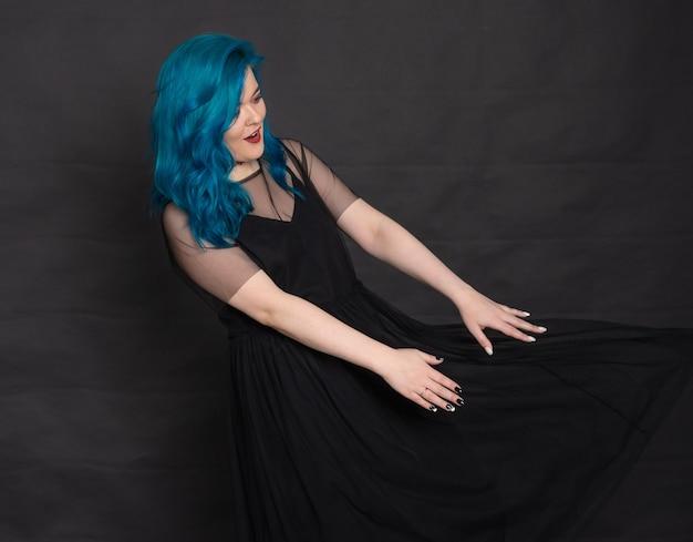 사람, 패션, 머리 개념 - 검은색 바탕에 파란 머리를 한 검은 드레스에 파란 머리를 한 재미있는 젊은 여성의 초상화