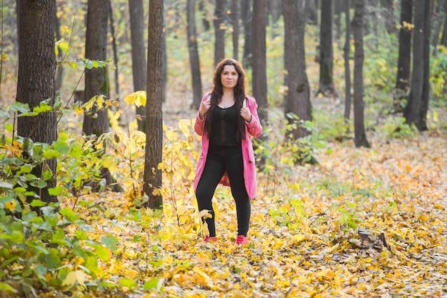 사람, 패션 및 자연 개념-가을 공원에 서있는 플러스 사이즈 여자