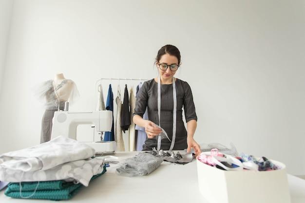 人、ファッション、ショールームのコンセプト-ショールームの若いファッションデザイナー。