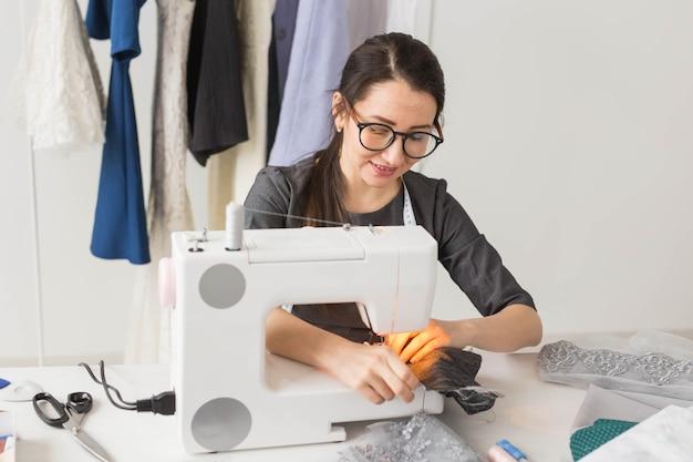 人、ファッション、ショールームのコンセプト-若いファッションデザイナーがミシンで服を縫う