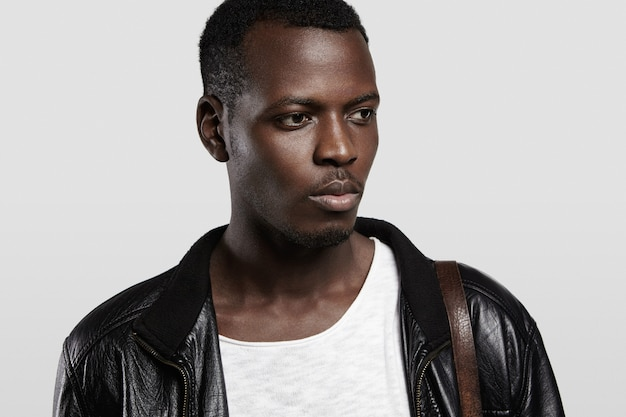 People and fashion. attractive fashionable dark-skinned man in stylish black leather jacket looking away with pensive face expression.