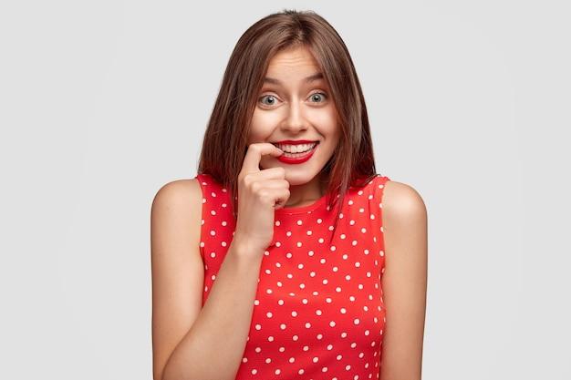 Persone e concetto di moda. bella giovane femmina ridacchia positivamente, tiene il dito vicino alla bocca, vestita con un elegante abito rosso, ha lunghi capelli scuri, nota qualcosa di divertente, isolato sopra il muro bianco